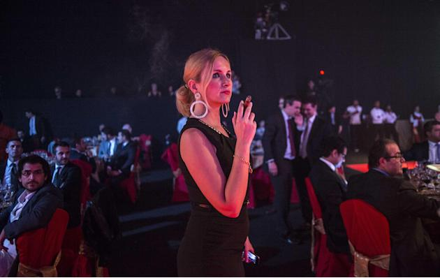 In this Feb. 27, 2015 photo, a woman smokes a cigar during a gala dinner marking the end of the 17th Cigar Festival in Havana, Cuba. Cuban cigar makers are licking their chops over new U.S. rules that