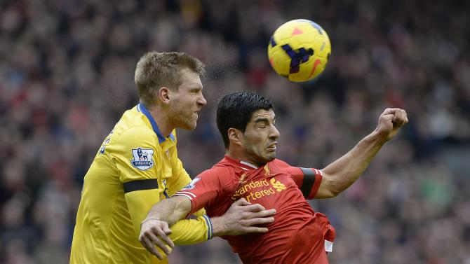 Liverpool's Suarez challenged by Arsenal's Mertesacker during their English Premier League soccer match at Anfield Stadium in Liverpool