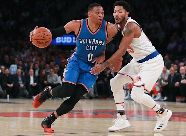 Oklahoma City Thunder's Russell Westbrook drives to the basket defended by the New York Knicks's Derrick Rose as he notches up five straight triple-doubles
