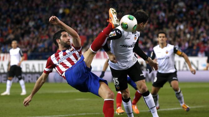 Atletico Madrid's Raul Garcia and Valencia's Javi Fuego fight for the ball during their Spanish King's Cup soccer match in Madrid