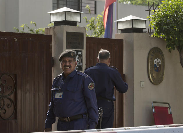 Pakistani guards stand alert outside the embassy of the Philippines where a national flag is at half-mast mourning the reported death of Ambassador Domingo Lucenario Jr. in Islamabad, Pakistan, Friday