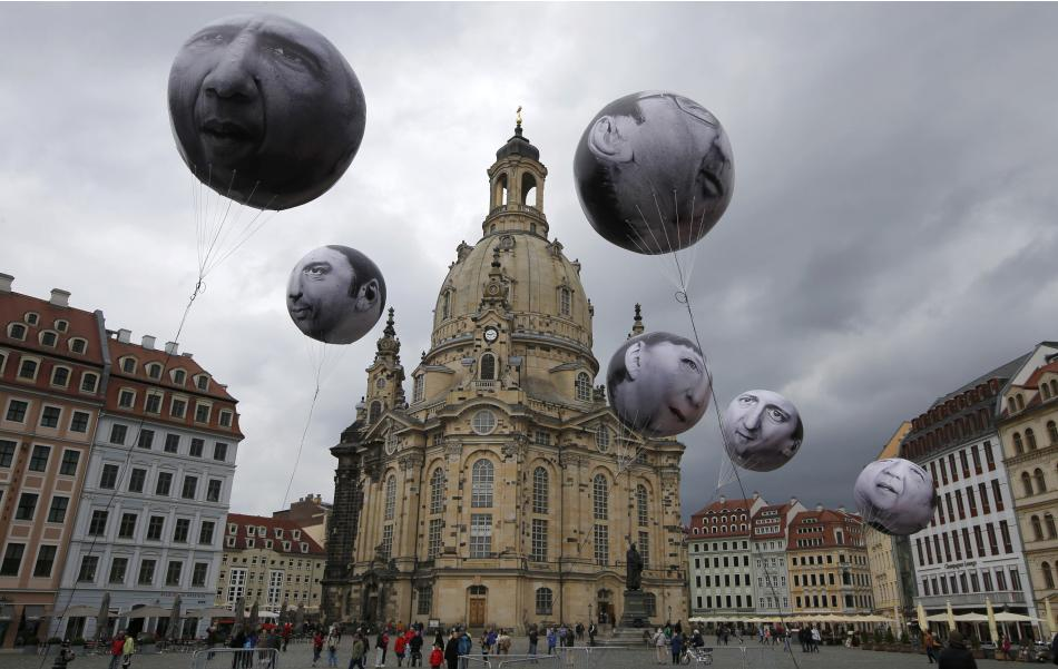People watch balloons made by the 'ONE' campaigning organisation  depicting leaders of the countries members of the G7 in front of the Frauenkirche cathedral in Dresden