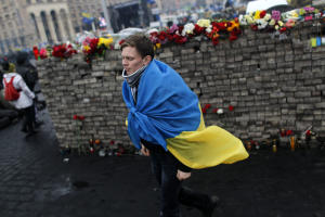 A youth draped in Ukraine's flag passes by a memorial …