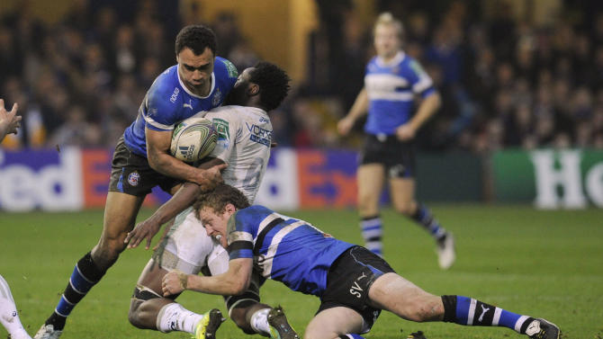 Bath's Olly Woodburn, left, and Sam Vesty, right, combine to tackle Montpellier's Fulgence Ouedraogo, centre, during their Heineken Cup pool 3 rugby match at the Recreation ground, Bath, England, Sunday, Nov. 20, 2011. (AP Photo/Tom Hevezi)