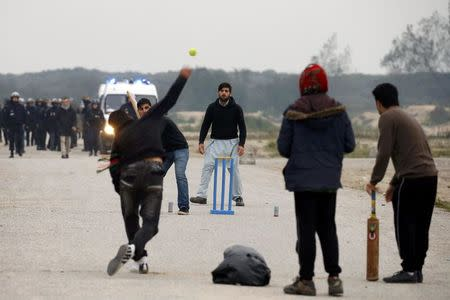 """French CRS riot police secure a road as migrants play cricket on the eve of the evacuation and dismantlement of the camp called the """"Jungle"""" in Calais"""