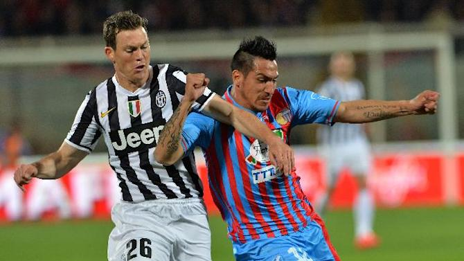 Juventus defender Stephan Lichtsteiner, left, of the Switzerland, vies for the ball with Catania defender Fabian Monzon, of Argentina, during a Serie A soccer match at the Angelo Massimino stadium in Catania, Italy, Sunday, March 23, 2014