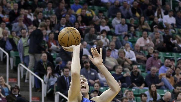 Dallas Mavericks' Dirk Nowitzki, left, shoots as Utah Jazz's Jeremy Evans (40) looks on in the second quarter during an NBA basketball game Wednesday, March 12, 2014, in Salt Lake City