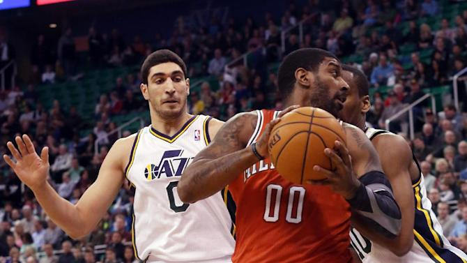 Milwaukee Bucks' O.J. Mayo (00) looks for the basket as he is defended by Utah Jazz's Enes Kanter (0) and Utah Jazz's Alec Burks, right, in the first half of an NBA basketball game Thursday, Jan. 2, 2014, in Salt Lake City