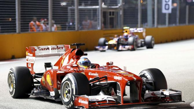 Ferrari Formula One driver Alonso races ahead of Red Bull Formula One driver Webber during the Singapore F1 Grand Prix in Singapore