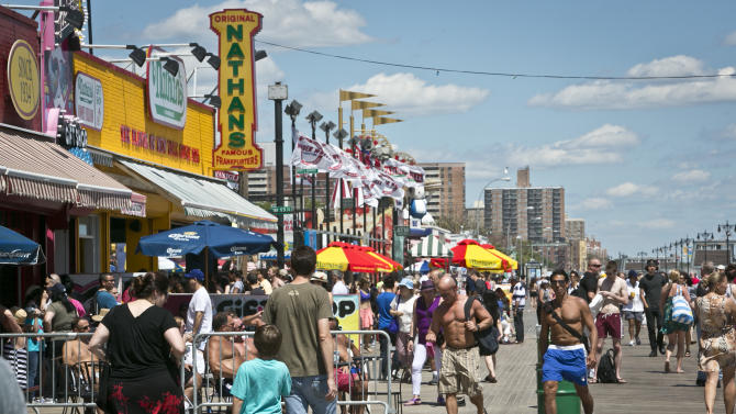 This June 12, 2013 photo shows visitors crowding a section of the boardwalk in the Coney Island section in the Brooklyn borough of New York. (AP Photo/Bebeto Matthews)