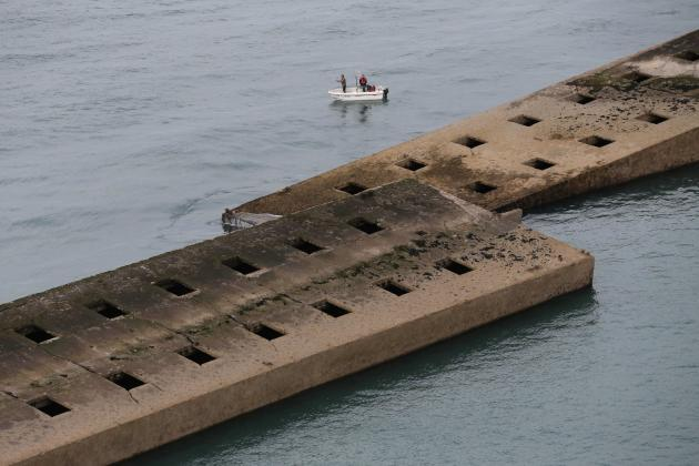 An aerial view shows people standing on a small boat next to the remains of Mulberry Harbour at Arromanches in the Normandy region