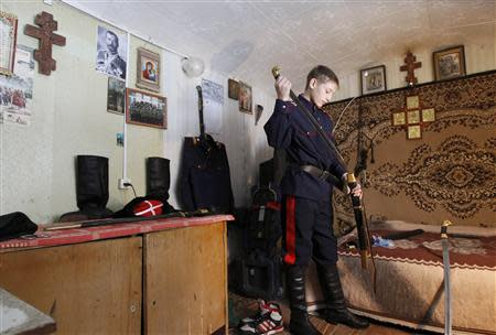 Russian Cossack Timoshenko sheathes a sword after juggling it, in the town of Krasny Oktyabr on the outskirts of the southern Russian city of Volgograd
