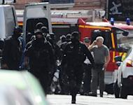 French rapid-intervention GIPN police units leave the area after police stormed a bank in Toulouse, arresting a gunman with psychiatric problems who claimed to be an Al-Qaeda militant. Two hostages were freed after a seven-hour siege