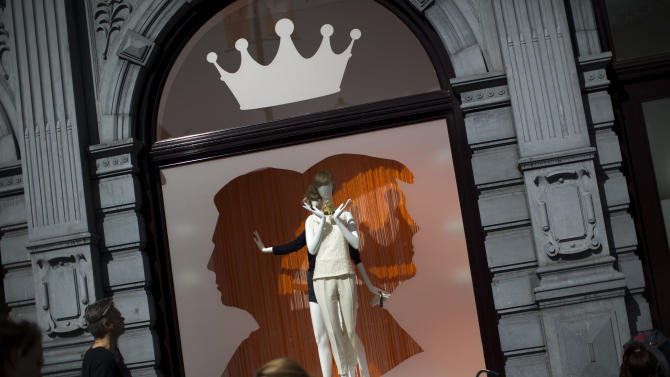 People walk near a shop decorated with a silhouette of Dutch Crown Prince Willem-Alexander and his wife Princess Maxima in Dam square in downtown Amsterdam, Netherlands Monday, April 29, 2013. Queen Beatrix has announced she will relinquish the crown on April 30, 2013, after 33 years of reign, leaving the monarchy to her son Crown Prince Willem-Alexander. (AP Photo/Emilio Morenatti)
