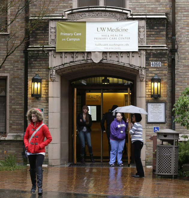 In this Dec. 11, 2014 photo, pedestrians exit the University of Washington's Hall Health Primary Care Center in Seattle. An unintended side-effect of federal health care reform is leading colleges
