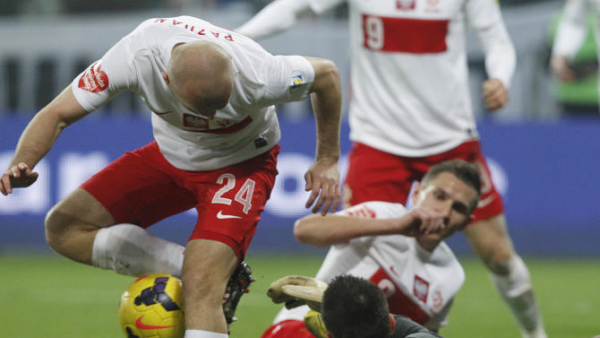 Poland's Michal Pazdan, left, and Marcin Robak, and Slovakia's goalkeeper Matus Kozacik, right, challenge for the ball during their friendly soccer match in Wroclaw, Poland, Friday, Nov. 15, 2013