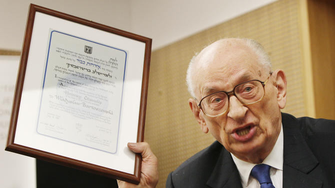Wladyslaw Bartoszewski, a Pole who survived Auschwitz and later helped save Jews from the Holocaust shows a copy of his honorary citizenship of Israel document during a ceremony at the Museum of the History of Polish Jews in Warsaw, Poland, Wednesday, Oct. 9, 2013 in which he offered Holocaust-era documents as a contribution to the museum's collection that is to open next year. (AP Photo/Czarek Sokolowski)