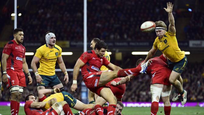 Wales's Mike Phillips clears the ball as Australia's Michael Hooper tries to charge the ball down during their international rugby union match in Cardiff