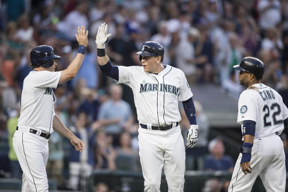 Seattle Mariners' Logan Morrison, center, celebrates hitting a three-run home run with teammates Seth Smith, left, and Robinson Canó in the fifth inning of a baseball game against the Detroit Tige