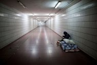 A homeless man lies on his bed in an underpass in Beijing on December 7, 2012. China's stated aim to narrow the income gulf between its sports-car driving elite and vast numbers who still live in poverty will need radical political and economic changes to work, say economists