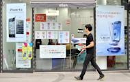 A man walks past signboards of Samsung Electronics' Galaxy S3 (R) and Apple's iPhone 4s (S) at a mobile phone shop in Seoul on August 24, 2012. A Seoul court ruled on August 24, 2012 that Apple and Samsung had infringed on each other's patents on mobile devices, and ordered a partial ban on sales of their products in South Korea
