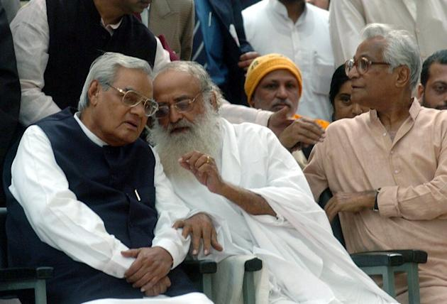 Self-styled godman Asharam (C) talks to former Indian Prime Minister Atal Bihari Vajpayee (L) at a hunger-strike rally to protest against the arrest of a Hindu religious leader, in New Delhi, on November 23, 2004. Asharam sparked a backlash on Tuesday after saying a 23-year-old student could have averted a murderous gang-rape by begging for mercy from her attackers