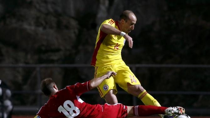 Romania's Iasmin Latovlevici fights for the ball with Andorra's Josep Manel Ayala during their 2014 World Cup qualifying soccer match at Estadi Comunal in Andorra