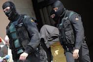 Spanish Civil Guards escort a suspected Al-Qaeda member after his arrest in the eastern Spanish city of Valencia on March 27, 2012. Spanish police arrested three suspected Al-Qaeda members thought to have been planning an attack in Spain or elsewhere in Europe and seized enough explosives to blow up a bus, the government said Thursday