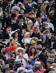 Racegoers photograph the arrival of Britain's Queen Elizabeth II on Derby Day, the second day of the Epsom Derby horse racing festival, at Epsom in Surrey on June 2, 2012 the first official day of Britain's Queen Elizabeth II's Diamond Jubilee celebrations. She received a rapturous welcome from a flag-waving crowd of more than 100,000 at a British racecourse Saturday