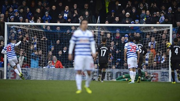 Norwich City goalkeeper Mark Bunn saves a penalty kick from Queens Park Ranger's Adel Taarabt (L) during their English Premier League soccer match at Loftus Road