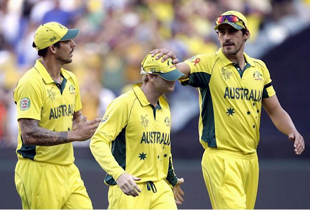 Australia's Starc celebrates with team mates Johnson and Smith as they walk off the field after dismissing New Zealand during their Cricket World Cup final match at the MCG