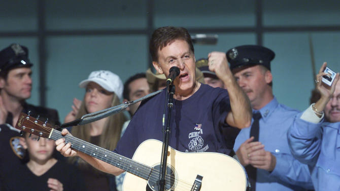 "FILE- In this Saturday, Oct. 20, 2001 file photo, Paul McCartney is surrounded on stage by New York City rescue workers at the end of the ""Concert for New York,"" at New York's Madison Square Garden. McCartney turned 70 years of age Monday June 18, 2012. (AP Photo/Beth A. Keiser, File)"