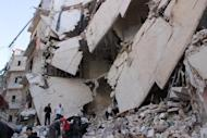 Rescue workers and civilians inspect ruble of a destroyed building following an airstrike reportedly by government forces on the Bustan al-Qasr rebel-held neighbourhood of the northern Syrian city of Aleppo on June 7, 2014