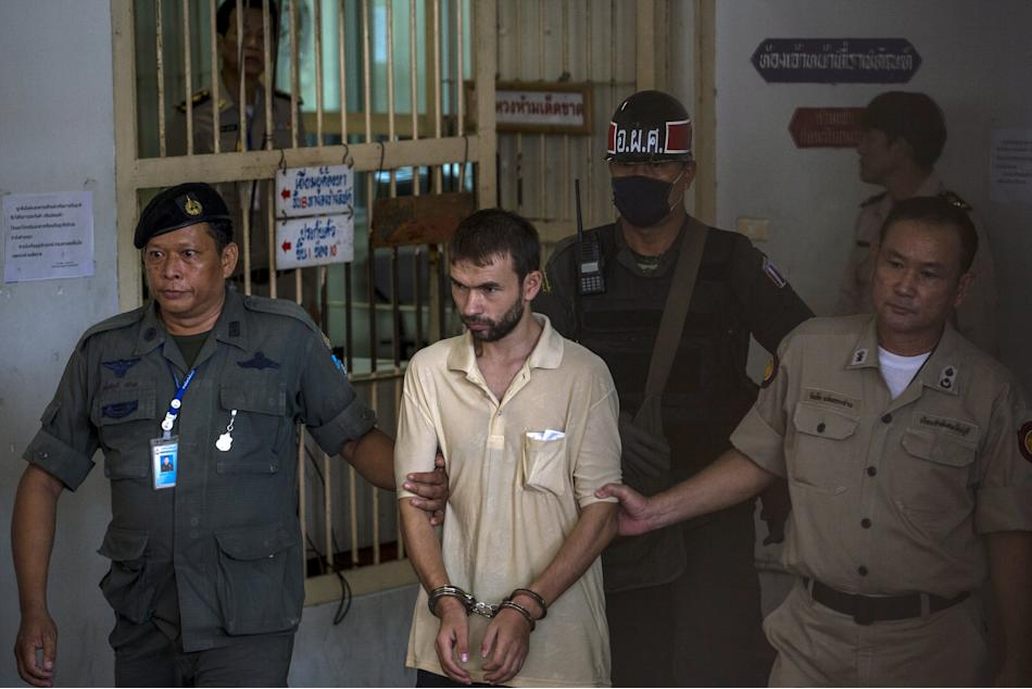 An arrested suspect of the recent Bangkok blast is escorted by police officers as he leaves a court in Bangkok