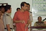 Thai-born US citizen Joe Wichai Commart Gordon arrives at the Criminal Court in Bangkok in December 2011. The 55-year-old was arrested in May on a visit to the kingdom and accused of posting the material deemed offensive online -- a banned biography of King Bhumibol Adulyadej that he translated into Thai -- while living in the United States