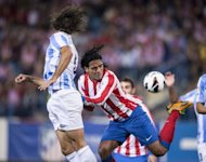Atletico Madrid's Radamel Falcao Garcia (R) fights for the ball with Malaga's Martin Demichelis during their Spanish La Liga match against Malaga, at Vicente Calderon stadium in Madrid, on October 7. On Sunday, Atletico face a tough away game at Real Sociedad who have won their three home games to date this season