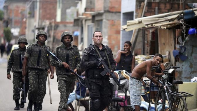 A policeman escorts Brazilian Army soldiers during an operation in the Mare slums complex in Rio de Janeiro