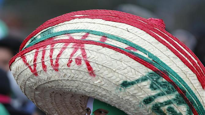 A vendor sells oversized Mexican style hats and team colored face masks at the stadium ahead of a 2014 World Cup qualifying match between Mexico and New Zealand in Mexico City, Wednesday, Nov. 13, 2013. Mexico has yet another coach and a last chance to reach next year's World Cup in Brazil