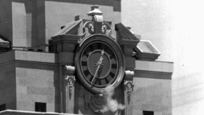 "FILE - In this Aug. 1, 1966, file photo, smoke rises from the sniper's gun as he fired from the tower of the University of Texas administration building in Austin, Texas, on crowds below. Police identified the slayer as Charles Whitman, a student at the university. The new documentary ""Tower"" about the shooting spree captures a sense of terror and confusion that was unprecedented then as it has become chilling commonplace today. (AP Photo/File)"