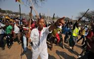 Thousands of miners of South Africa's strike-hit platinum belt gather for a rally on September 13 in Rustenurg. South African police have fired tear gas to disperse workers at platinum giant Lonmin's Marikana mine after raiding hostels and seizing traditional weapons in a crackdown on growing mining unrest