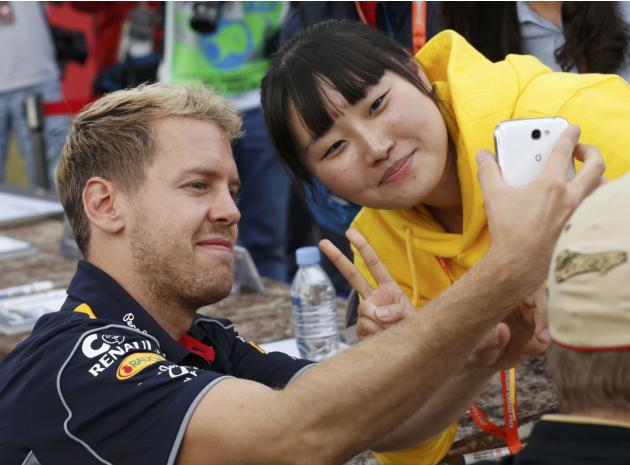 Red Bull Formula One driver Vettel takes a photograph with a fan after the qualifying session for the Korean F1 Grand Prix in Yeongam