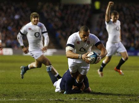 England's Luther Burrell scores a try as Scotland's Greig Laidlaw attempts a tackle during their Six Nations rugby union match at Murrayfield Stadium in Edinburgh