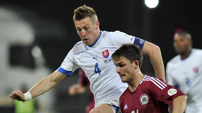 Latvia's Valerijs Sabala, right, vies for the ball with Slovakia's Jan Durica during a World Cup 2014 Group G qualification match in Riga, Latvia, on Tuesday. October 15, 2013