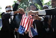 "Pakistani lawyers burn a US flag as they attempt to reach the US embassy in the diplomatic enclave during a protest against an anti-Islam movie in Islamabad on September 19. More than 30 people worldwide have died in incidents linked to the trailer for ""Innocence of Muslims,"" a US-made film that depicts the Prophet Mohammed as a thuggish womaniser."