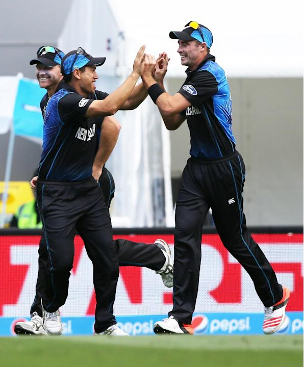 New Zealand's Tim Southee, right, is congratulated by teammate Ross Taylor after taking a catch to dismiss South African batsman Quinton De Kock during their Cricket World Cup semifinal in Auckland, N
