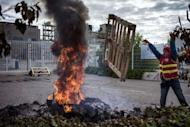 An employee of Kem One throws a wooden pallet into a fire during a protest over job cuts on May 14, 2013 outside the company factory in Pierre-Benite, south of Lyon in central eastern France. In March, the number of unemployed French jobseekers reached a record-high, hitting 3.224 million.