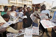 People gather around a newspaper stand on March 6, 2013 in Kisumu