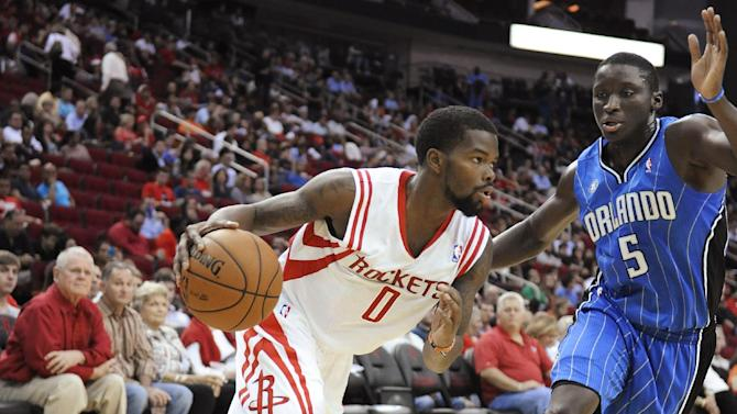 Houston Rockets' Aaron Brooks (0) drives the ball past Orlando Magic's Victor Oladipo in the second half of a preseason NBA basketball game Wednesday, Oct. 16, 2013, in Houston
