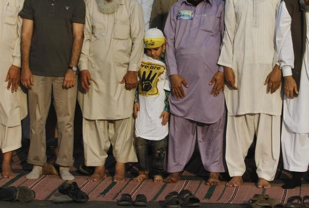 A boy stands between supporters of Jamaat-e-Islami and the Pakistan Tehreek-e-Insaf political party, as they perform evening prayers during a protest in Karachi