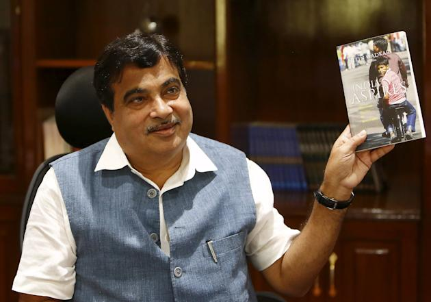 Gadkari displays a book written by him at his office in New Delhi
